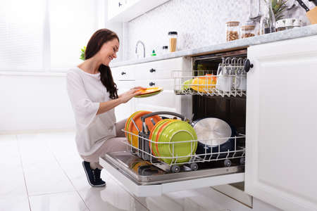 Smiling Young Woman Arranging Plates In Dishwasher At Home