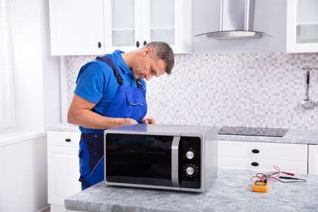 Side View Of Mature Man Repairing Microwave Oven In Kitchen