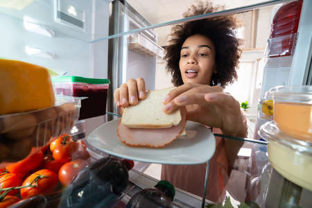 Hungry Woman Taking Fresh Ham Sandwich From Plate In The Refrigerator
