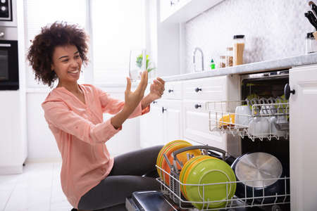 Happy Young Woman Checking Washed Transparent Drinking Glass Near The Dishwasher