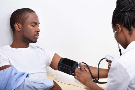 Close-up de la mano del médico midiendo la presión arterial del paciente masculino