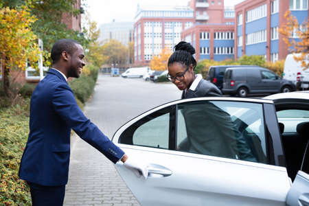 Happy African Male Valet Opening Door For Businesswoman Getting Out Of A Car On Street Stock Photo