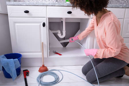 A Young Woman Cleaning Clogged Sink Pipe With Drained Cable In The Kitchen