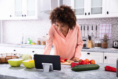 Happy Young African Woman Using Digital Tablet While Chopping Vegetables In The Kitchen