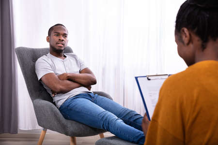 Young African Man Sitting On Chair Near Female Psychologist With Clipboard