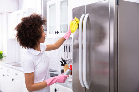Close-up Of Serious Young Woman Cleaning Refrigerator With Yellow Napkin And Spray Detergent Фото со стока