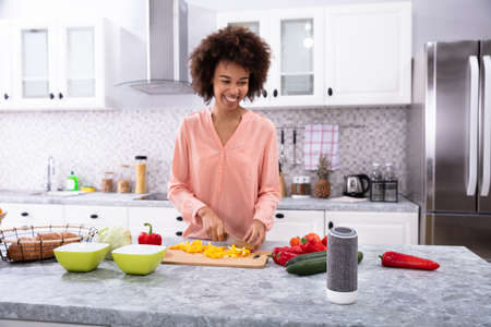 Young Happy African Woman Cutting Yellow Bell Pepper On Chopping Board In The Kitchen 免版税图像