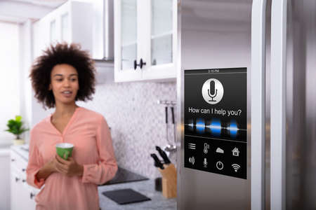 Young Woman Holding Green Coffee In Hand Looking At Refrigerator With Voice Recognition Function Фото со стока