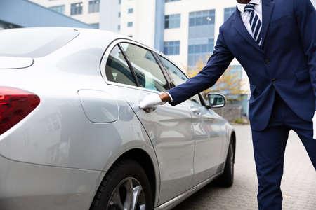 Mano del valet abriendo la puerta del coche gris en la calle Foto de archivo