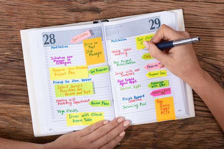 Draufsicht einer Geschäftsfrau, die mit Stift auf dem Schreibtisch Zeitplan in das Tagebuch schreibt