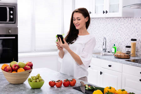 Smiling Young Woman Using Cellphone Near Fresh Fruits And Vegetables On Kitchen Counter 免版税图像