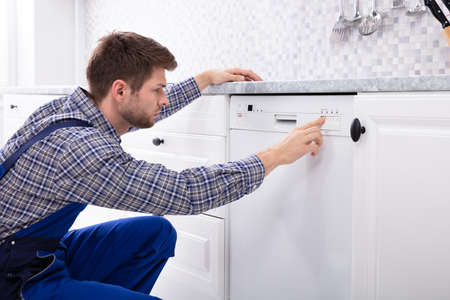 Young Serviceman Pressing Button Of Dishwasher In Kitchen