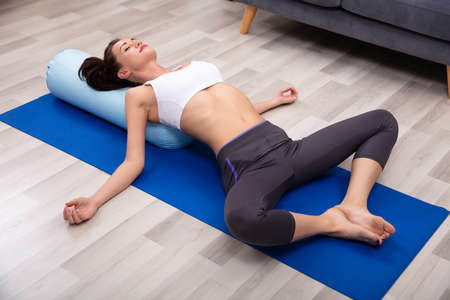 Young Woman Practicing Yoga On Bolster At Home Stockfoto