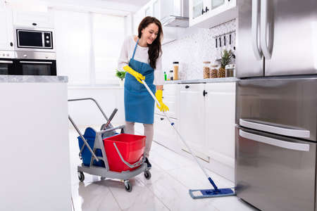Happy Female Janitor Cleaning Floor With Mop In Kitchen 写真素材