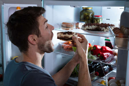Portrait Of A Happy Man Eating Cake Near Open Refrigerator