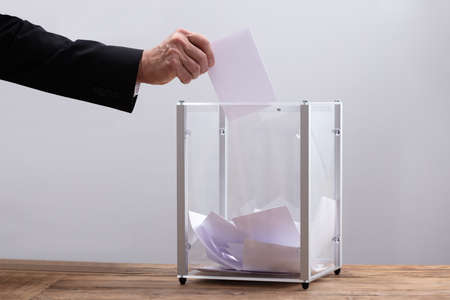 Close-up Of Businessman's Hand Inserting Ballot In A Glass Box 版權商用圖片