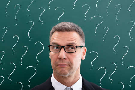 Thinking Mature Man In Front Of Question Marks Drawn On Chalkboard Imagens - 116478646