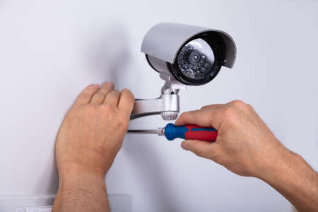 Close-up Of Male Technician Adjusting Cctv Camera On Wall With Screwdriver