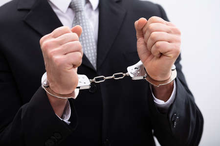 Photo of criminal businessman arrested wearing handcuffs Stock Photo