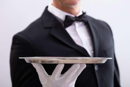 Close-up de la mano del camarero sosteniendo la bandeja de plata vacía contra el fondo blanco.