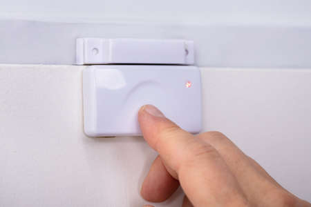Close-up Of A Person's Finger Pressing Security System Door Sensor Stok Fotoğraf