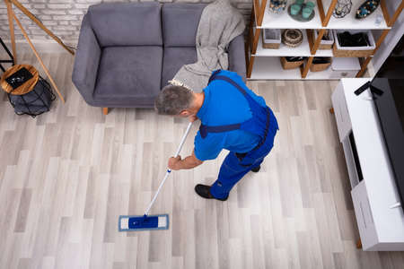Mature Male Janitor Cleaning Floor With Mop At Home