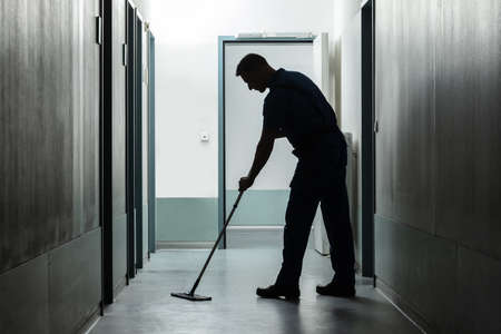 Side View Of Man Cleaning Floor With Mop Stock Photo