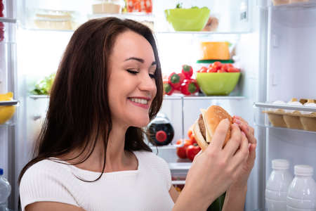 Smiling Young Woman Looking At Burger Standing In Front Of Refrigerator