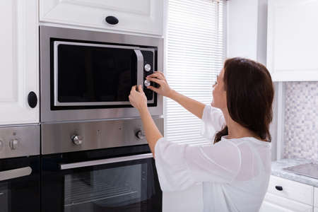 Side View Of A Young Woman Using Microwave Oven In Kitchen Imagens