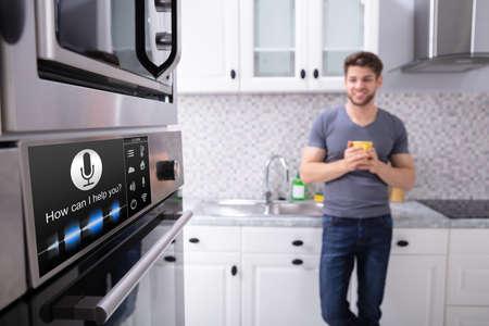 Feliz joven mirando el horno con función de reconocimiento de voz en la cocina
