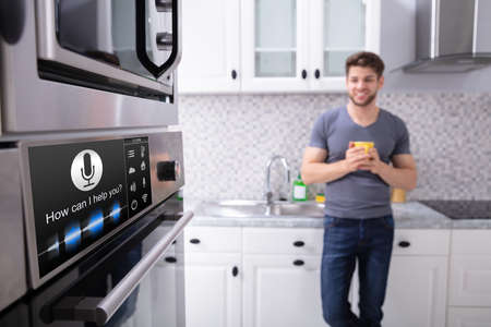 Happy Young Man Looking At Oven With Voice Recognition Function In Kitchen