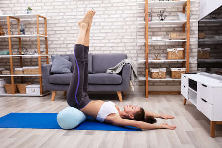 Young Woman Doing Stretching Exercise On Blue Yoga Mat
