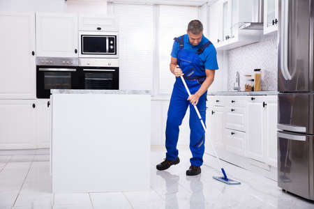 Side View Of A Male Janitor Cleaning White Floor With Mop In The Kitchen