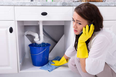 Sad Young Woman Calling Plumber In Front Of Water Leaking From Sink Pipe Reklamní fotografie