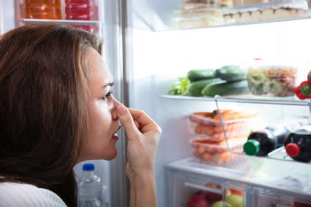 Side View Of Young Woman Recognizing Bad Smell Coming From The Refrigerator