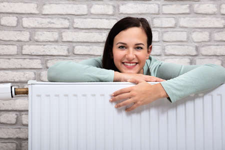 Portrait Of A Happy Young Woman Leaning On Heating Radiator Banque d'images