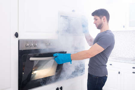Young Man Wearing Gloves Opening Oven Filled With Smoke In Kitchen 스톡 콘텐츠