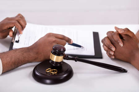 Close-up Of A Judge Explaining Contract To His Client With Gavel And Golden Rings