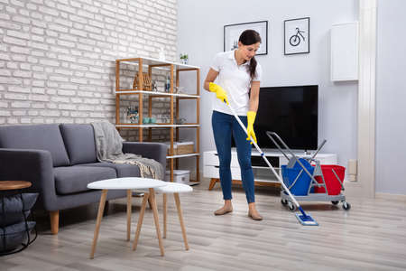Female Janitor Cleaning Floor With Mop In Living Room