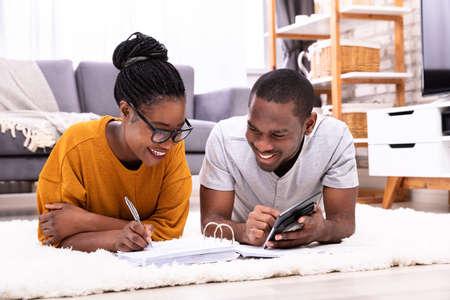 Młoda para afrykańska leżąca na fakturze dywanowej z kalkulatorem Zdjęcie Seryjne