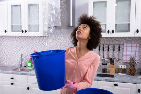 Close-up Of A Worried Young Woman Collecting Water Leaking From Ceiling In The Blue Bucket