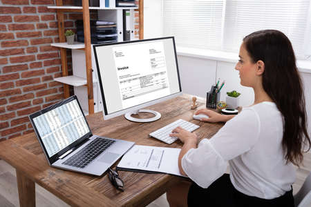 Young Businesswoman Looking At Invoice On Computer Screen In The Office