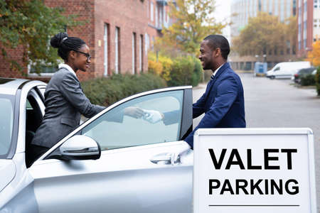Smiling Businesswoman Giving Car Key To Male Valet Near Valet Parking Sign