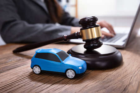Close-up Of Mallet, Gavel And Blue Toy Car In Front Of A Person Using Laptop Stock Photo