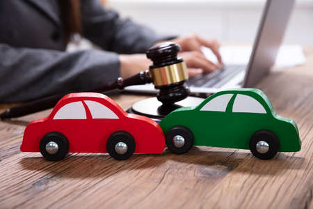 Small Green And Red Car In Front Of Gavel And Mallet And Businessperson Using Laptop