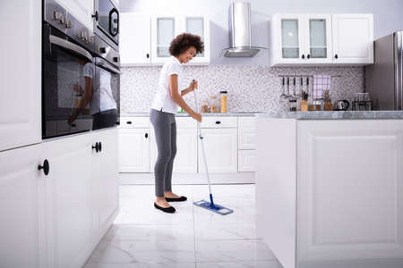 Side View Of A Smiling Female Janitor Cleaning White Floor With Mop In The Kitchen 版權商用圖片