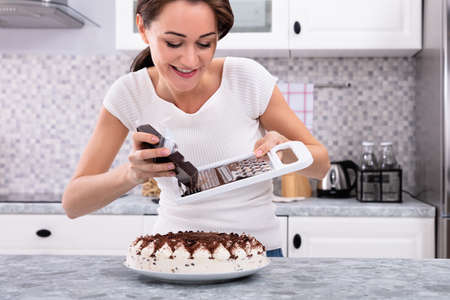 Portrait Of A Smiling Young Woman Grating Chocolate Over Cake