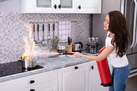 Woman Using Fire Extinguisher To Stop Fire On Burning Cooking Pot In The Kitchen