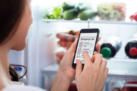 Close-up Of A Womans Hand Marking Shopping List On Mobile Phone