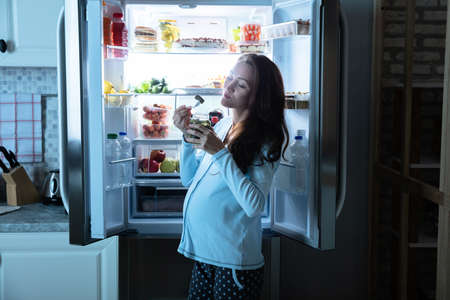 Pregnant Woman Eating Pickle From Jar In Front Of An Open Refrigerator 免版税图像